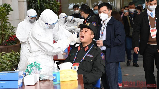 Health workers in protective suits collect nasal-throat samples from staff members at the National Convention Centre in Hanoi, where the 13th National Party Congress is taking place. (Photo: NDO)