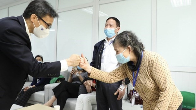 Deputy Prime Minister Vu Duc Dam visits volunteers participating in the second trial phase of Nano Covax. (Photo: VNA)
