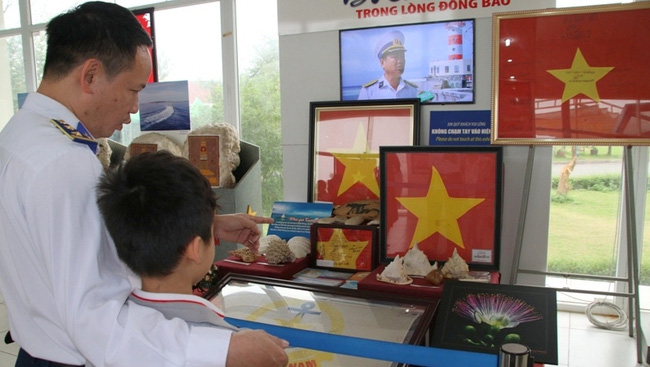 A naval soldier and his son admiring works on display at the exhibition. (Photo: Vietnam National Village for Ethnic Culture and Tourism)