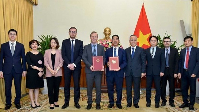 Representatives of Vietnam and the UK hand over notes confirming the date when the UKVFTA comes into force. (Photo: VNA)