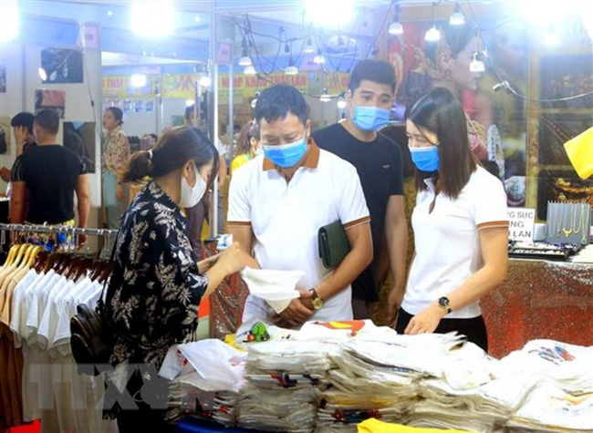 Visitors go shopping at booths at the event (Photo: VNA)
