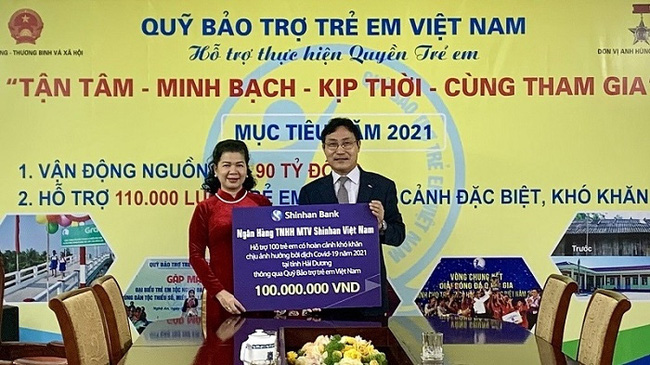 Le Tuyet Mai, Deputy Director of the National Fund for Vietnamese Children, receives a token representing VND100 million to support Hai Duong children from Cho Mun Sung, Deputy General Director of Shinhan Bank Vietnam.