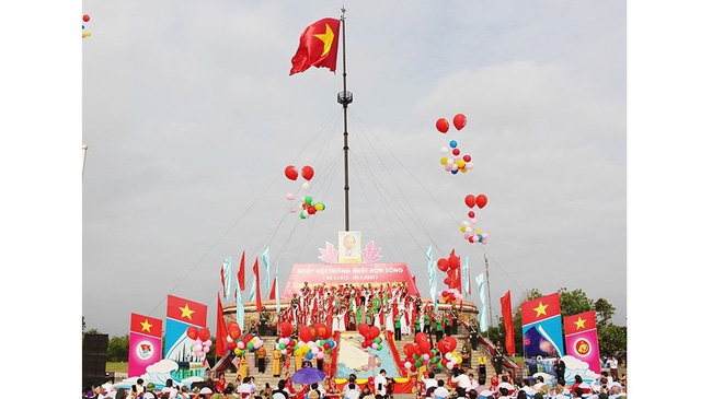 National flag being raised at the Hien Luong - Ben Hai historic site in Vinh Linh District, Quang Tri Province on April 30, 2021. (Photo: NDO/Lam Quang Huy)