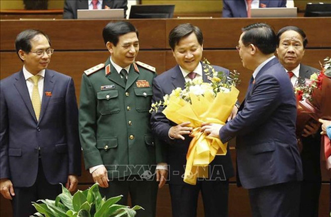 NA Chairman Vuong Dinh Hue presents flowers to newly-appointed Deputy PM Le Minh Khai (2nd from right).