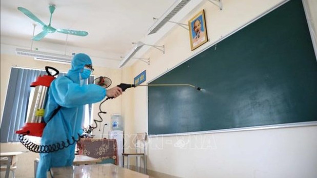 A health worker sprays disinfectant in a classroom (Photo: VNA)