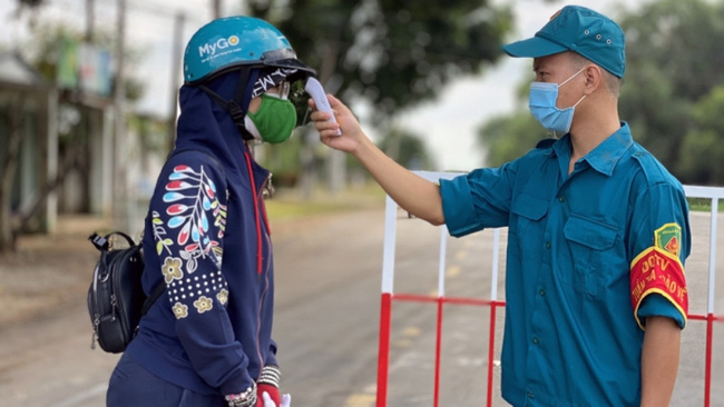 Cheking body temperature of a visitors at a health quarantine checkpoint