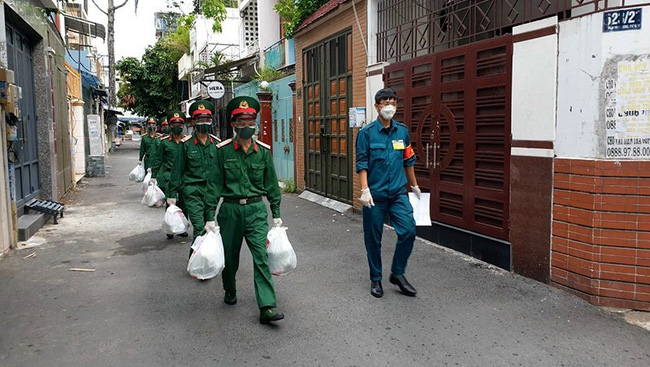 Soldiers go to the market and bring necessities to locals in District 10 in Ho Chi Minh City. (Photo: Phuoc Thien)