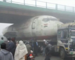 Xe tải chở máy bay mắc kẹt dưới gầm cầu