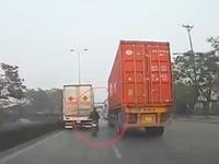 Xe máy liều lĩnh 'len' giữa xe tải và container