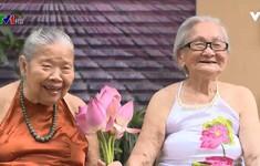 Hai cụ bà mặc yếm đào chụp ảnh với hoa sen