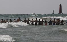 Nhiều người dân nắm tay nhau tạo thành sợi dây sống để cứu hộ người đuối nước