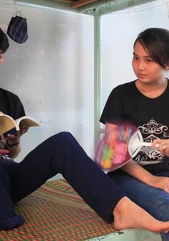 Chị gái ngồi quạt mát cho em trai khuyết tật ôn thi