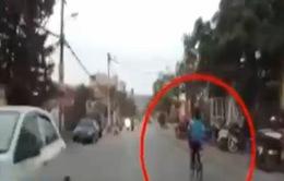Vừa đạp xe, vừa múa hát, bé trai ngã nhào trước đầu ô tô