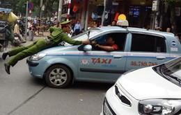 """Hà Nội: Cảnh sát """"đu mình"""" trên nắp capo xe taxi tại phố Bà Triệu"""