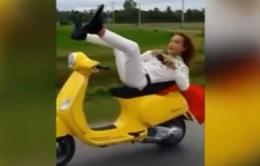 Nam thanh niên nằm dài trên yên, lái xe máy bằng chân