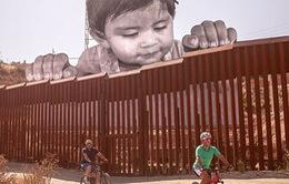 Chân dung bé trai di cư khổng lồ ngó qua biên giới Mỹ - Mexico