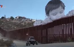 Chân dung cậu bé khổng lồ nhìn qua bức tường biên giới Mỹ - Mexico