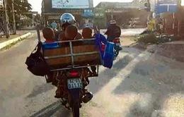 Người phụ nữ chở 4 em nhỏ trong lồng sắt, chạy như bay trên đường