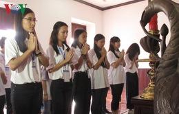 Thanh niên kiều bào dâng hương hoa tại tượng đài Bác ở Bến Nhà Rồng