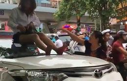 """Nữ tài xế taxi leo lên nóc xe """"ăn vạ"""" khi CSGT bắt lỗi vượt đèn đỏ"""