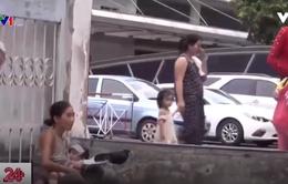 Bế trẻ em xin tiền trước cổng bệnh viện để tiêm chích ma túy