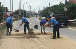 Thanh tra giao thông dọn cát rơi vãi giữa đường Hà Nội