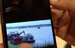 Chủ tịch Nguyễn Đức Chung cho phóng viên xem clip khai thác cát lậu cạnh tàu cảnh sát