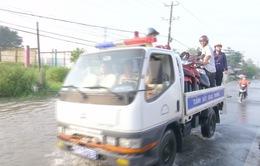 Công an Vĩnh Long chở xe máy giúp dân qua đoạn Quốc lộ ngập sâu