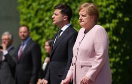 Thủ tướng Đức Angela Merkel run bần bật khi chào cờ