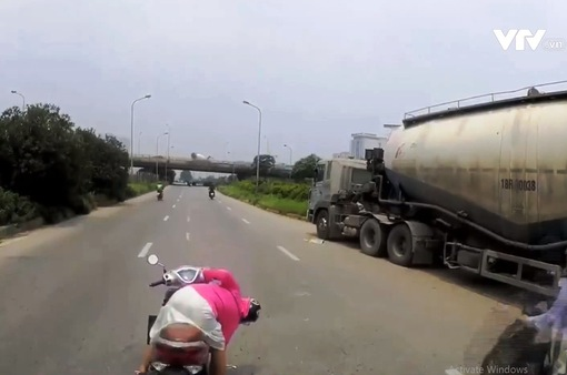 Vô tư dừng đột ngột trước đầu xe tải để... nhặt đồ đánh rơi