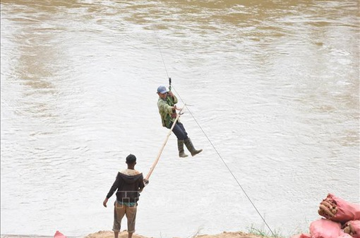 """Cầu treo bị lũ cuốn trôi, người dân liều mình với """"tử thần"""" đu dây vượt sông"""