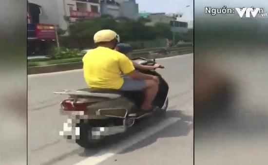 Giật mình em bé lái xe đèo bố giữa phố Hà Nội