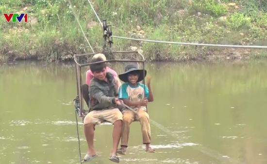 Bất chấp nguy hiểm, người dân liều mình đu dây cáp qua sông Pô Kô