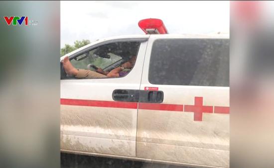 Tài xế xe cứu thương nghe điện thoại, gác chân khi lái xe