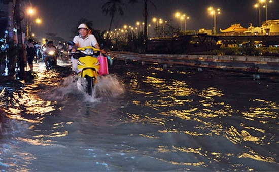 Người dân TP.HCM bì bõm đẩy xe trong dòng nước đen ngòm